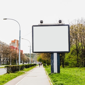 Aanplakbord met lamp twee dichtbij de stoep in de stad