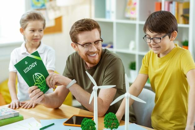 Aanrakende modellen. glimlachende bebaarde leraar die blij is met de interesse van zijn jonge leerlingen en hen materialen uitlegt