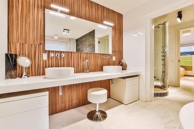 Aanrechtblad met twee wastafels en kasten aan muur met houten tegel en spiegel met lampen in badkamer