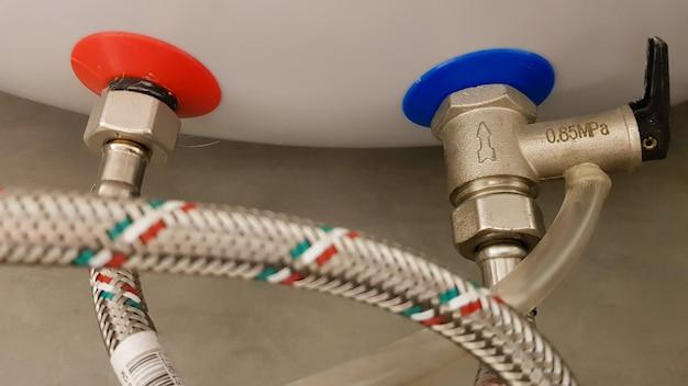Aansluiting van watertoevoer, warm en koud water op de ketel. slang voor warm en koud water in de badkamer. sanitair aansluitingen voor een huishoudelijke elektrische boiler.