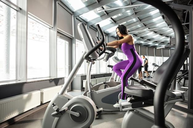 Aanstaande. jonge gespierde blanke vrouw oefenen in de sportschool met cardio. atletisch vrouwelijk model dat snelheidsoefeningen doet, haar onderlichaam traint. wellness, gezonde levensstijl, bodybuilding.