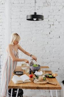 Aanstaande moeder die salade in de keuken bereidt