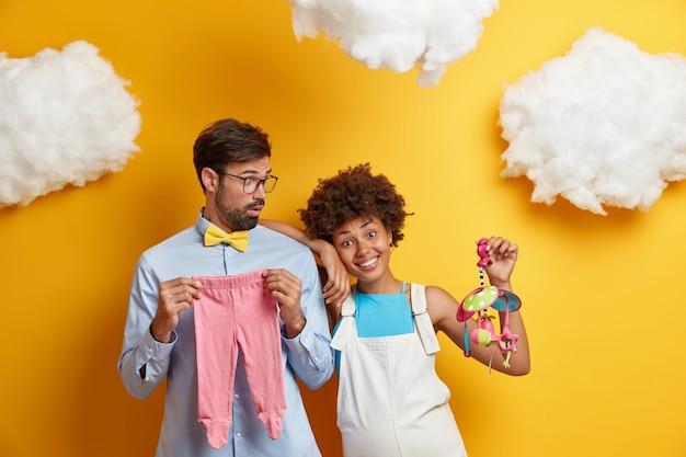 Aanstaande moeder en vader poseren met speelgoed en babykleding, bereid je voor om binnenkort ouders te worden. toekomstige moeder op haar late zwangerschapsperiode, houdt mobiel vast, heeft grote buik, geïsoleerd op gele muur.