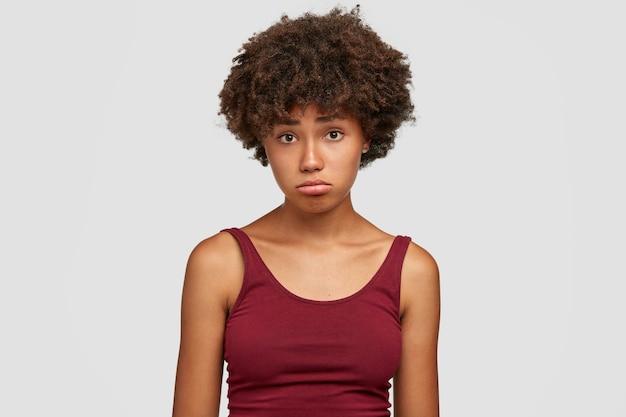 Aanstootgevend zwart meisje tuit de lippen met een uitdrukking van ontevredenheid, voelt frustratie, wordt terneergeslagen door negatief nieuws