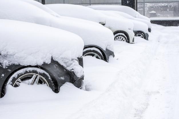 Aantal geparkeerde auto's bezaaid met sneeuw, zicht op de voorwielkap en bumper.