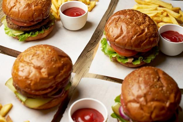 Aantal hamburgers met frietjes en ketchupsaus. grote hamburgers en frietjes op houten tafel achtergrond. fastfood achtergrond instellen. restaurant hamburgermenu