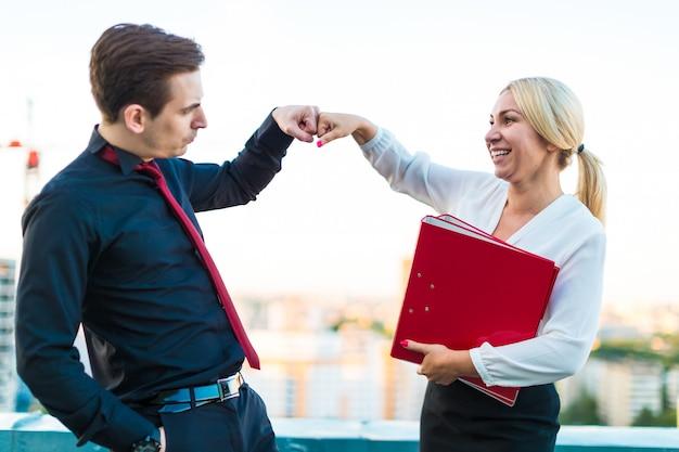 Aantal zakenlieden, jonge brunette man en jonge schoonheid blonde vrouw staan op het dak met papieren map