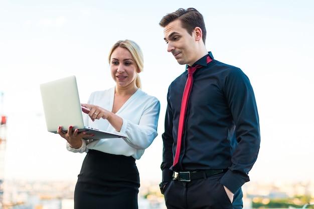Aantal zakenlieden, serieuze brunette man en aantrekkelijke blonde vrouw staan op het dak en kijken in laptop