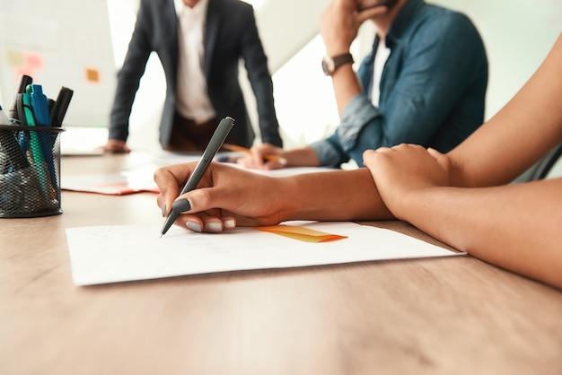 Aantekeningen maken. bijgesneden beeld van een vrouw die iets opschrijft terwijl ze met collega's in een modern kantoor zit. zakelijke bijeenkomst