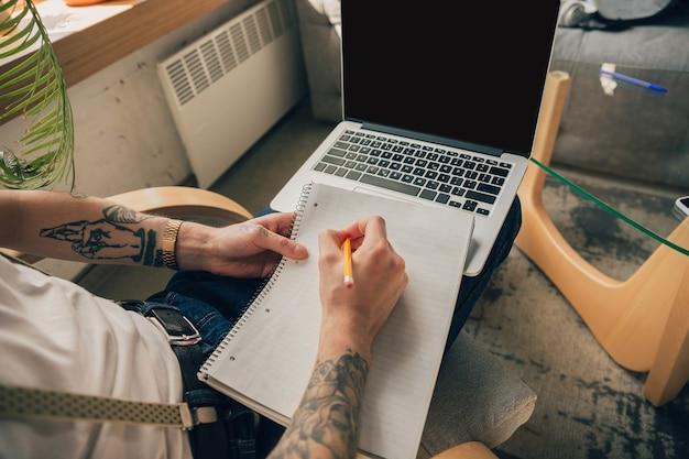 Aantekeningen maken. man studeert thuis tijdens online cursussen, slimme school