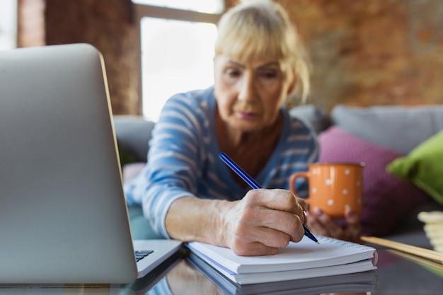 Aantekeningen maken tijdens de les. senior vrouw thuis studeren, online cursussen krijgen