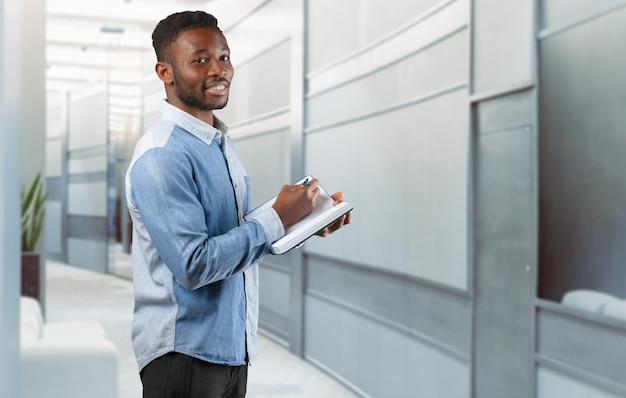 Aantekeningen maken. vrolijke jonge afrikaanse zakenman die iets in zijn blocnote schrijft