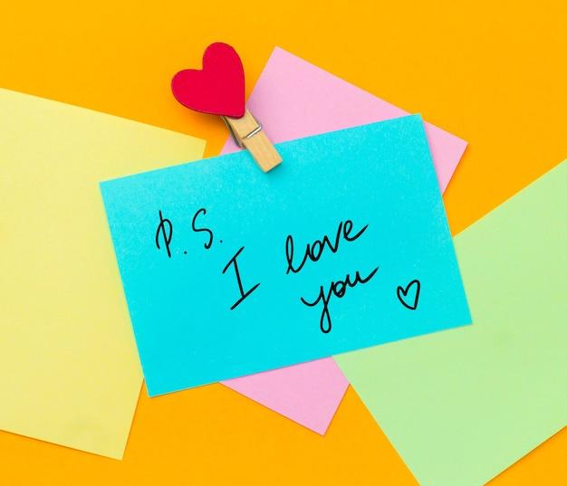 Aantekeningen op papier met tekst ps ik hou van je met stoffen speld versierd met hart