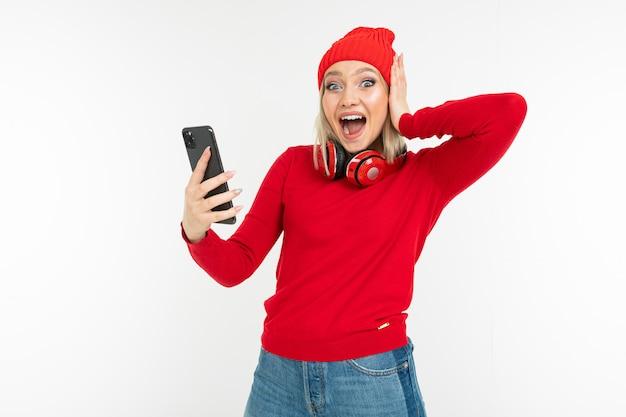 Aantrekkelijk actief meisje zoekt muziek via een applicatie op een smartphone op een witte achtergrond