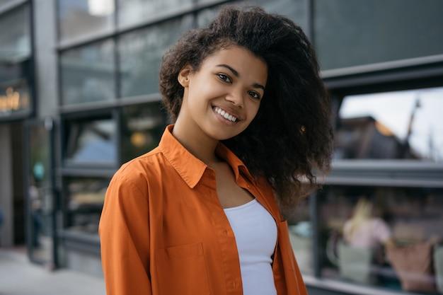 Aantrekkelijk african american meisje met mooi gezicht en stijlvolle krullend haar lachend