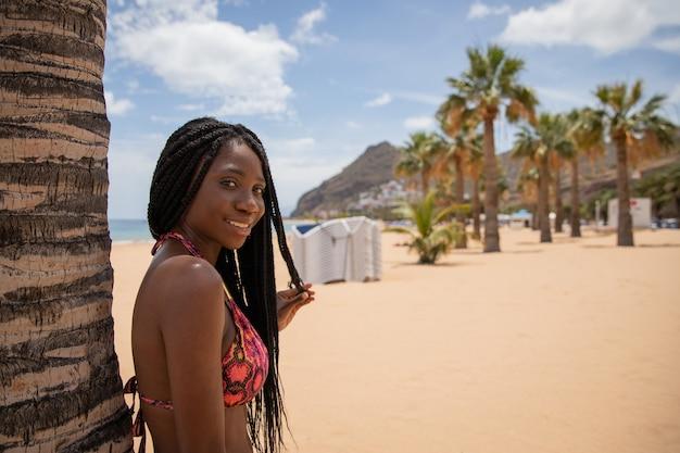 Aantrekkelijk afrikaans meisje geniet van haar vakantie op het strand, ze leunt met haar rug op een palmboom en raakt haar vlechten aan met haar hand.