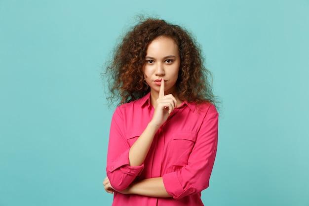 Aantrekkelijk afrikaans meisje in casual kleding zeggen stilte wees stil met vinger op lippen shhh gebaar geïsoleerd op blauwe turkooizen achtergrond. mensen oprechte emoties levensstijl concept. bespotten kopie ruimte.