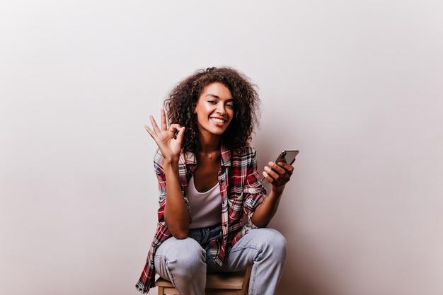 Aantrekkelijk afrikaans meisje poseren met goed teken. krullende zwarte dame met romantische smartphone van de glimlachholding.