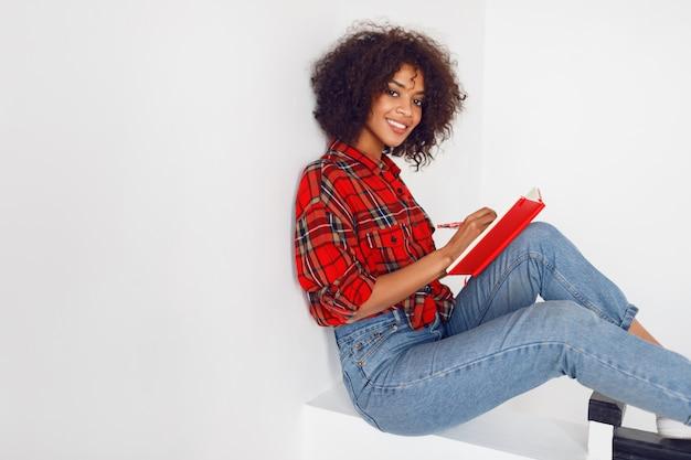Aantrekkelijk afrikaans studentenmeisje dat met notitieboekje rust. het dragen van rood geruit overhemd. blauwe spijkerbroek.