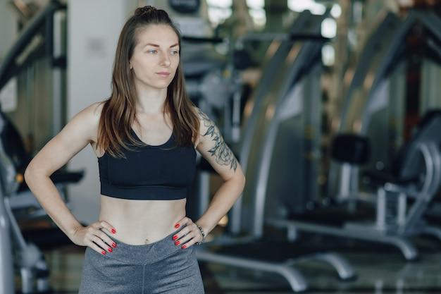 Aantrekkelijk atletisch meisje staat op de achtergrond van simulatoren in de sportschool. gezonde levensstijl.