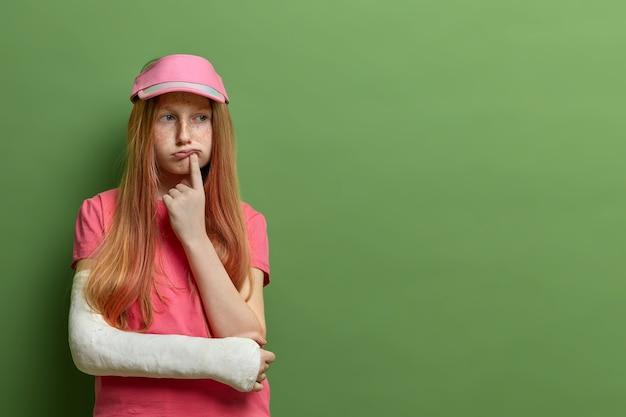 Aantrekkelijk, attent, mooi roodharig meisje kijkt opzij en denkt diep over iets na, draagt een gegoten arm, staat tegen een groene muur, lege ruimte voor je
