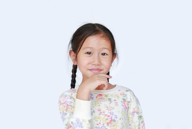 Aantrekkelijk aziatisch klein kindmeisje glimlachend en hand op kin aan te raken