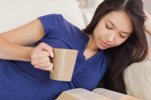 Aantrekkelijk aziatisch meisje die op de bank liggen die een roman lezen en hete drank drinken