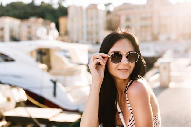 Aantrekkelijk blij meisje met bronzen huid die zwarte zonnebril houdt en buiten met boten rust