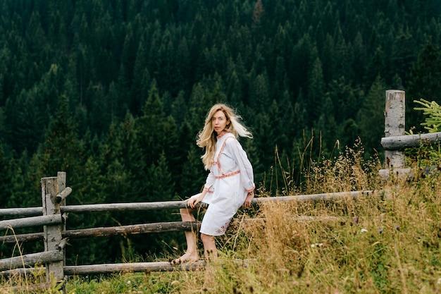 Aantrekkelijk blond meisje in witte jurk met borduurwerk zittend op een houten hek over schilderachtig boslandschap