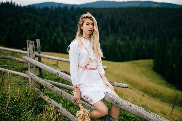 Aantrekkelijk blond meisje in witte jurk met ornament zittend op een houten hek met aartjes boeket over schilderachtig landschap van het platteland