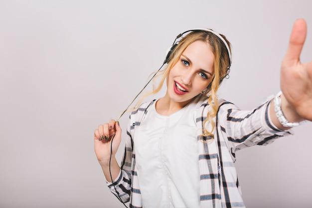Aantrekkelijk blond meisje in witte kleren met plezier en grappig dansen. schitterende krullende jonge vrouw die favoriete muziek in oortelefoons luistert.