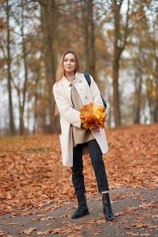 Aantrekkelijk blond meisje met boeket van oranje esdoornbladeren in de handen, het dragen van modieuze herfstjas, zwarte jeans en trendy zwart lederen laarzen wandelen in de herfst park.