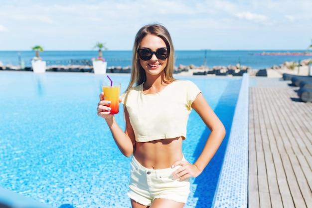 Aantrekkelijk blond meisje met lang haar staat in de buurt van zwembad. ze houdt een cocktail vast en lacht naar de camera.