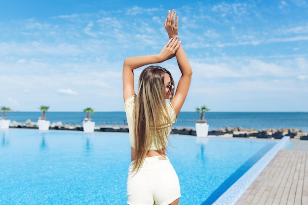 Aantrekkelijk blond meisje met lang haar staat in de buurt van zwembad. ze houdt haar handen boven. uitzicht vanaf de achterkant.