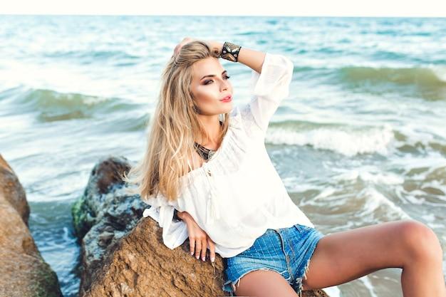 Aantrekkelijk blond meisje met lang haar zit op steen op zee achtergrond.