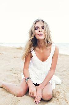 Aantrekkelijk blond meisje met lang haar zit op zand op het strand. ze kijkt naar de camera.