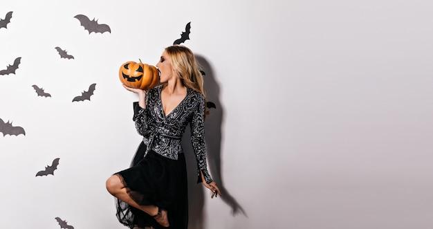 Aantrekkelijk blondemeisje die halloween-pompoen eten. geïnspireerde jonge vrouw poseren in heksenkleding.
