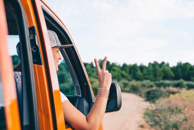 Aantrekkelijk blondemeisje die wapen in autoraam met v op vingers opstijgen