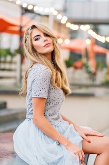 Aantrekkelijk blondemeisje in blauwe tule rokzitting op terrasachtergrond. ze houdt haar hand op het blote been en kijkt naar de camera.