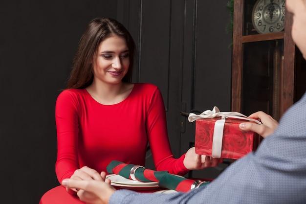 Aantrekkelijk cadeau voor een mooie vrouw in restaurant