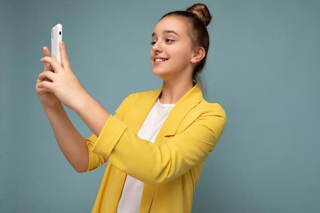 Aantrekkelijk charmant jong glimlachend gelukkig meisje die en mobiele telefoon gebruiken die selfie nemen die modieuze kleding dragen die over muur wordt geïsoleerd.