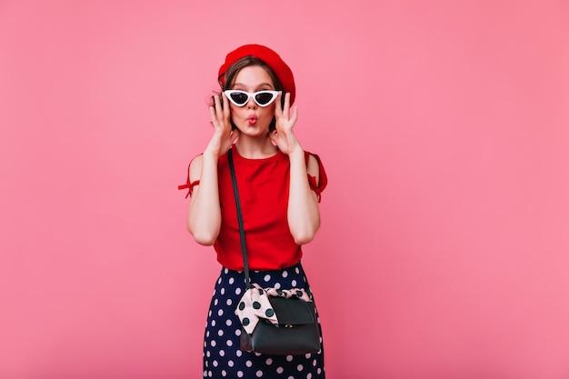 Aantrekkelijk donkerbruin meisje dat in zonnebril grappige gezichten maakt. charmant frans vrouwelijk model dat voor de gek houdt.