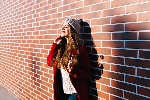 Aantrekkelijk donkerbruin meisje met lang haar op muur buiten. ze draagt een gebreide muts, een rode jas. houdt lolly rode lippen vast. lachend met gesloten ogen naar zonneschijn.
