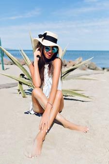 Aantrekkelijk donkerbruin meisje met lang haar zit op het strand in de buurt van de zee. ze raakt het been aan en kijkt naar beneden.