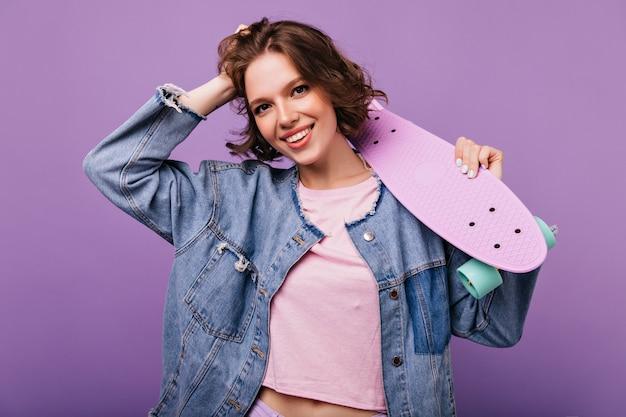 Aantrekkelijk donkerharig meisje poseren in spijkerjasje. winsome jonge vrouw met skateboard.
