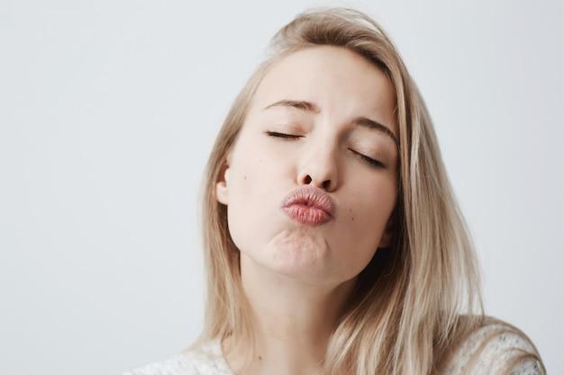 Aantrekkelijk dromerig vrouwelijk model met blond haar sluit ogen, pruilt lippen, stuurt kusjes