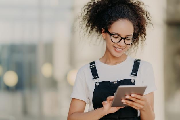 Aantrekkelijk duizendjarig meisje met fris haar, houdt digitale tablet, surft sociale netwerken, draagt optische bril