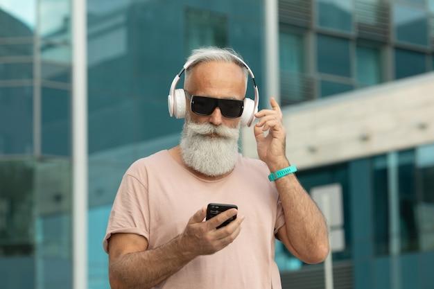 Aantrekkelijk en glimlachend bebaarde oude senior man met wit haar genieten van muziek van slimme telefoon buiten dragen witte koptelefoon.