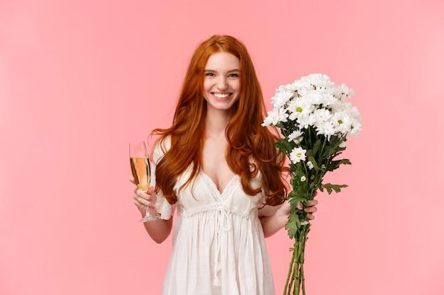 Aantrekkelijk en opgewonden romantische roodharige vriendin ontvangt geschenk, houdt witte boeket bloemen en glazen champagne vast, drinkt gelegenheid, heeft perfecte valentijnsdag, roze