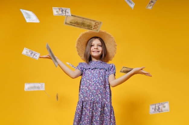 Aantrekkelijk europees meisje gooit geld in handen op een gele achtergrond